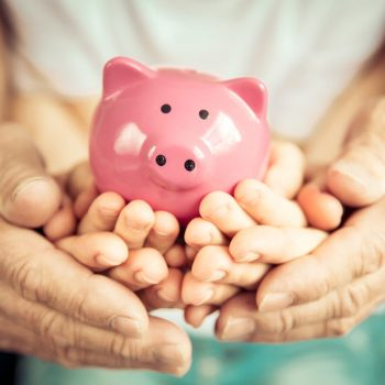 Family holding piggybank in hands. Investment concept